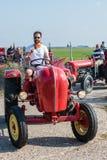 De mens met zonnebril en witte T-shirt op rode tractor geeft duim-omhooggaand aangezien hij begint te drijven stock afbeelding