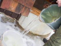 De mens in militaire eenvormig neemt water van een put in de winter op stock foto