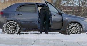 De mens nadert de auto opent de deur en neemt zijn handschoenen stock video