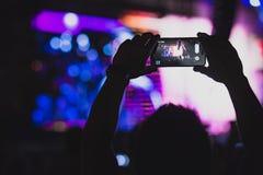 De mens neemt beelden op zijn smartphone bij overleg Stock Afbeelding