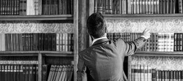 De mens neemt boek van boekenkast De studententribunes in bibliotheek en kiezen boek De kerel in slim kostuum leest dichtbij boek stock fotografie