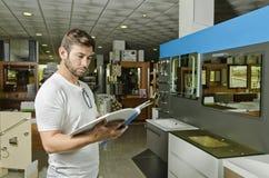 De mens neemt de inrichtingen en de badkamerss van de catalogusopslag waar Royalty-vrije Stock Afbeeldingen