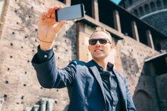 De mens neemt een zelfbeeld met zijn smartphone dichtbij het oude kasteel royalty-vrije stock afbeelding