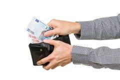 De mens neemt Euro bankbiljetten van portefeuille Stock Foto