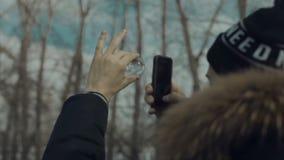De mens neemt foto op de telefoon door een glasbal stock footage