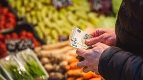 De mens neemt geld van portefeuille op markt stock afbeeldingen