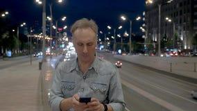 De mens neemt mobiele telefoon tegen het drijven van auto's bij nacht stock video