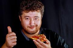 De mens in neemt smakelijke handen neemt een heerlijk stuk van pizza stock afbeelding