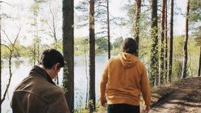 De mens neemt steen op en werpt het in meer terwijl het lopen in bos met vriend stock video