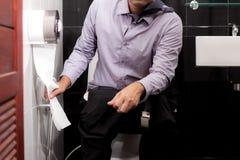 De mens neemt weefsel in badkamers Stock Fotografie