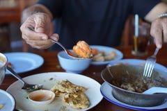 De mens nodigt om met onduidelijk beeldgarnalen en achtergrond te eten uit Royalty-vrije Stock Afbeeldingen