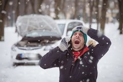 De mens is onder spanning omdat zijn opgesplitste auto De winterreis a stock afbeelding