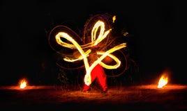De mens onderhoudt publiek met behulp van brand het dragen de nacht van brandprestaties Stock Afbeeldingen