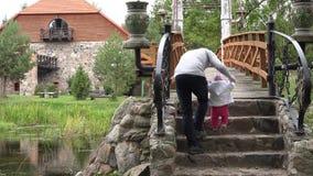 De mens onderwijst baby om op steentreden en houten brug over rivier te lopen 4K stock videobeelden