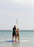De mens onderwijst een jongen om het windsurfing te berijden Stock Afbeelding