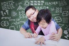 De mens onderwijst een meisje om op boek te schrijven Stock Foto
