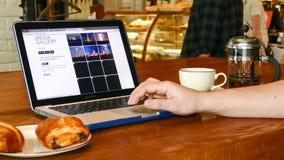 De mens onderzoekt Ruimtex-website op laptop het scherm in koffie Stock Foto's