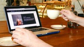 De mens onderzoekt Ruimtex-website op laptop het scherm in koffie Royalty-vrije Stock Fotografie