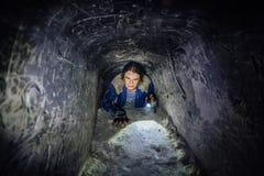 De mens onderzoekt smalle passage in oud verlaten ondergronds krijtachtig holklooster royalty-vrije stock foto's