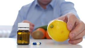 De mens onderzoekt Verse Vruchten zoals Alternatief aan Vitaminenbehandeling met Geneeskundepillen stock video