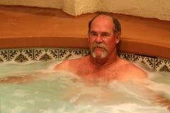 De mens ontspant in jacuzzi spa Stock Fotografie