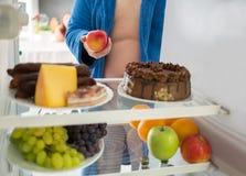 De mens op dieet neemt gezonde appel in plaats van hard voedsel Stock Fotografie
