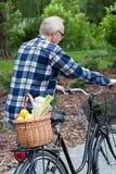 De mens op een fiets draagt een plantaardige mand Stock Afbeeldingen
