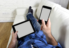 De mens op laag thuis woonkamer liggen die gelijktijdig mobiele telefoon met behulp van en de digitale tablet die vullen in Inter royalty-vrije stock foto