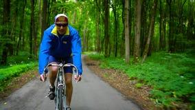De mens op middelbare leeftijd berijdt een wegfiets langs een bosweg, langzame motie stock footage
