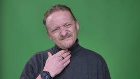 De mens op middelbare leeftijd in grijze trui lijdt aan keelpijn en het koude letten droevig op in camera op groene achtergrond stock videobeelden