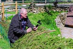 De mens op middelbare leeftijd maakt een videoopname op een mobiele telefoon met a royalty-vrije stock afbeelding