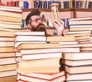 De mens op nadenkend gezicht houdt zandloper terwijl het bestuderen, boekenrekken op achtergrond Leraar of student met baard het  royalty-vrije stock foto