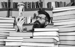 De mens op nadenkend gezicht houdt zandloper terwijl het bestuderen, boekenrekken op achtergrond De mens, wetenschapper in glazen royalty-vrije stock afbeelding