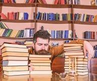 De mens op slaapgezicht legt tussen stapels van boeken, valt in slaap terwijl het bestuderen in bibliotheek, boekenrekken op acht royalty-vrije stock fotografie