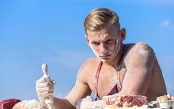 De mens op strikt gezicht met blondehaar draagt schort, hemel op achtergrond Chef-kokconcept Chef-kokkok die deeg voor baksel voo stock fotografie