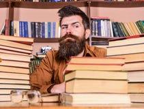 De mens op strikt gezicht zit tussen stapels van boeken, terwijl het bestuderen in bibliotheek, boekenrekken op achtergrond Leraa stock afbeeldingen