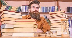 De mens op strikt gezicht zit tussen stapels van boeken, terwijl het bestuderen in bibliotheek, boekenrekken op achtergrond Leraa stock afbeelding