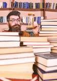 De mens op verrast gezicht houdt zandloper terwijl het bestuderen, boekenrekken op achtergrond Het Concept van de tijdstroom Lera royalty-vrije stock foto