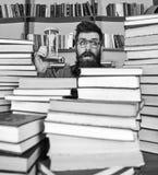 De mens op verrast gezicht houdt zandloper terwijl het bestuderen, boekenrekken op achtergrond Het Concept van de tijdstroom Mens royalty-vrije stock foto