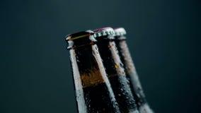 De mens opent drie flessen vers bier met schuim en dalingen stock video