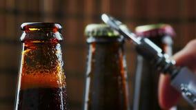 De mens opent drie flessen vers bier met schuim en dalingen op donkere bar als achtergrond stock video