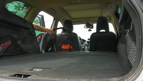De mens opent de vouwen van de autoboomstam onderaan zetels en begint te zuigen stock footage