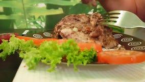 De mens overhandigt besnoeiingenlapje vlees op een plaat stock video