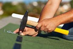 De mens overhandigt de vastmakende dakspanen van het bitumendak Royalty-vrije Stock Afbeeldingen