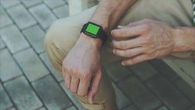 De mens overhandigt gebaren een modern slim horloge met een groene zeer belangrijke inhoud van de het schermchroma stock footage