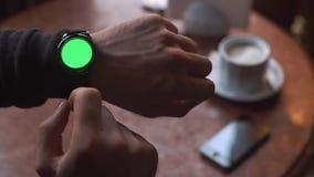De mens overhandigt gebaren op een ronde het scherm moderne smartwatch met een groene zeer belangrijke inhoud van de het schermch stock video
