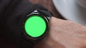 De mens overhandigt gebaren op een ronde het scherm moderne smartwatch met een groene zeer belangrijke inhoud van de het schermch stock videobeelden