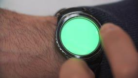De mens overhandigt gebaren op een ronde het scherm moderne smartwatch met een groene zeer belangrijke inhoud van de het schermch stock footage