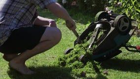 De mens in overhemd, die ontruimt van gras elektrische grasmaaimachine hurken stock videobeelden