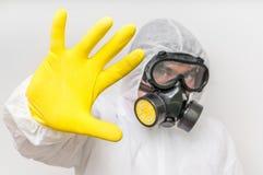 De mens in overtrekken met gasmasker toont eindegebaar stock afbeelding